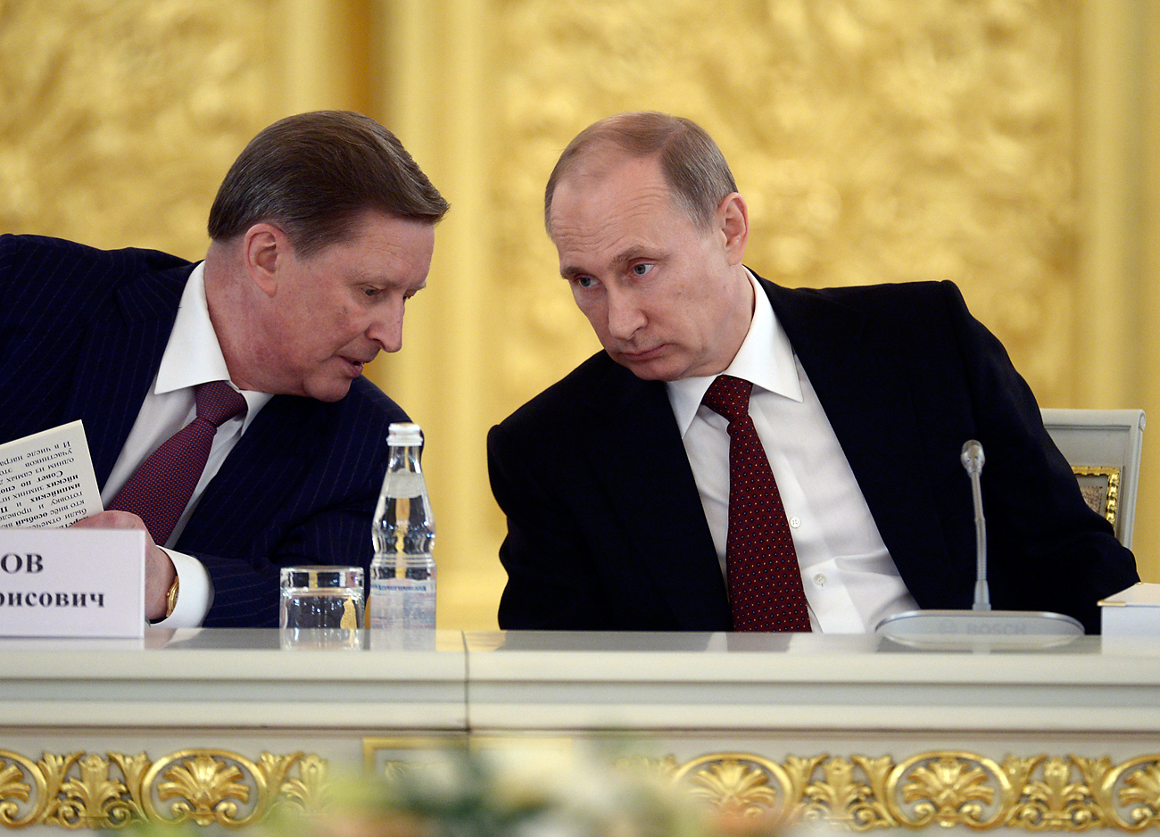 Russian President Vladimir Putin speaks with Sergei Ivanov, head of the presidential administration, during a government meeting in Moscow's Kremlin on March 24, 2014.