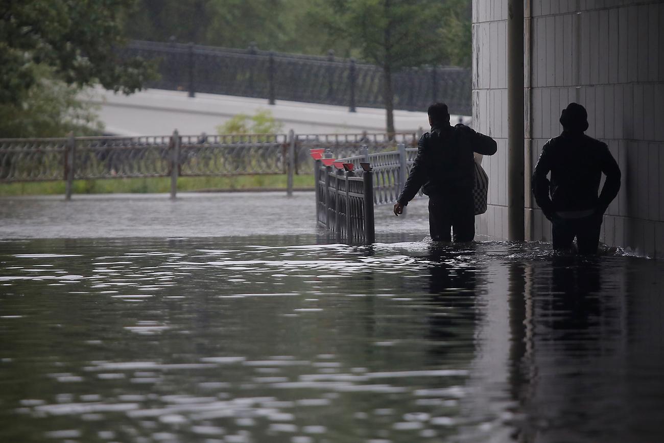 Dua orang pria berjalan menembus banjir selama hujan deras di kota Moskow, Rusia, 15 Agustus 2016.