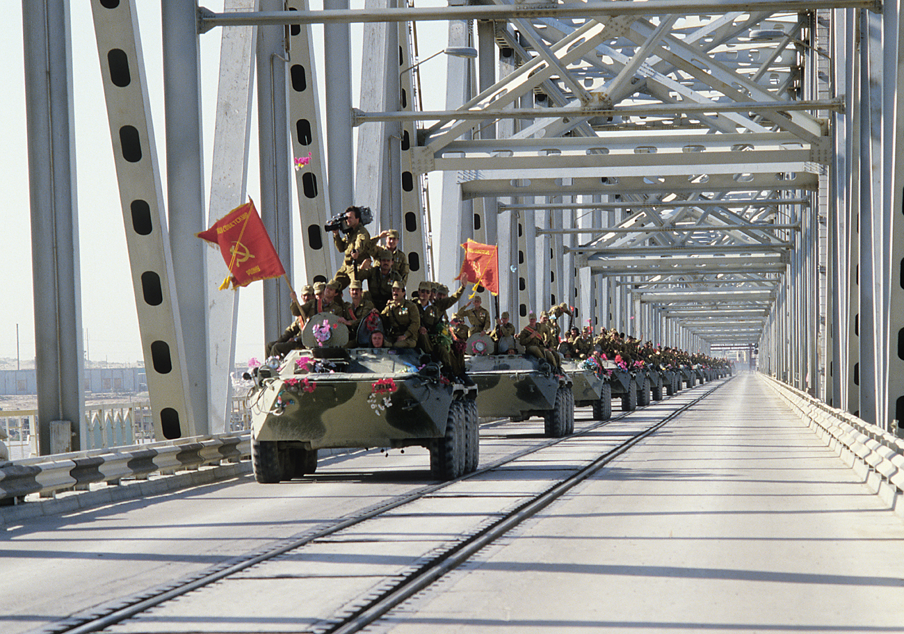 A column of armored vehicles crosses the Afghan-Soviet border on the Friendship Bridge over the Amu Darya River.