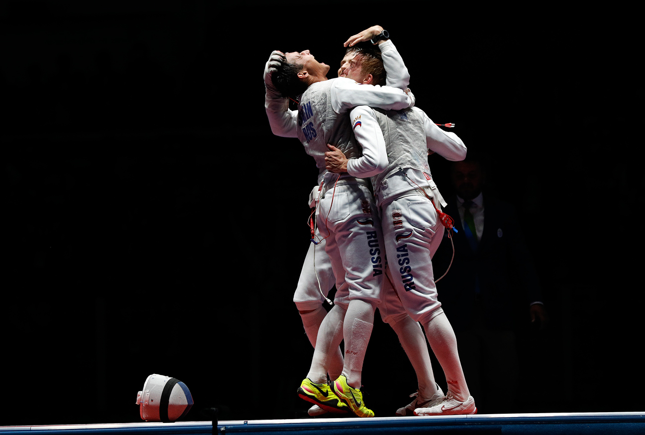 Timur Safin from Russia, celebrates with his teammate after defeating France during the Gold medal match in the men's team foil competition at the 2016 Summer Olympics in Rio de Janeiro, Brazil