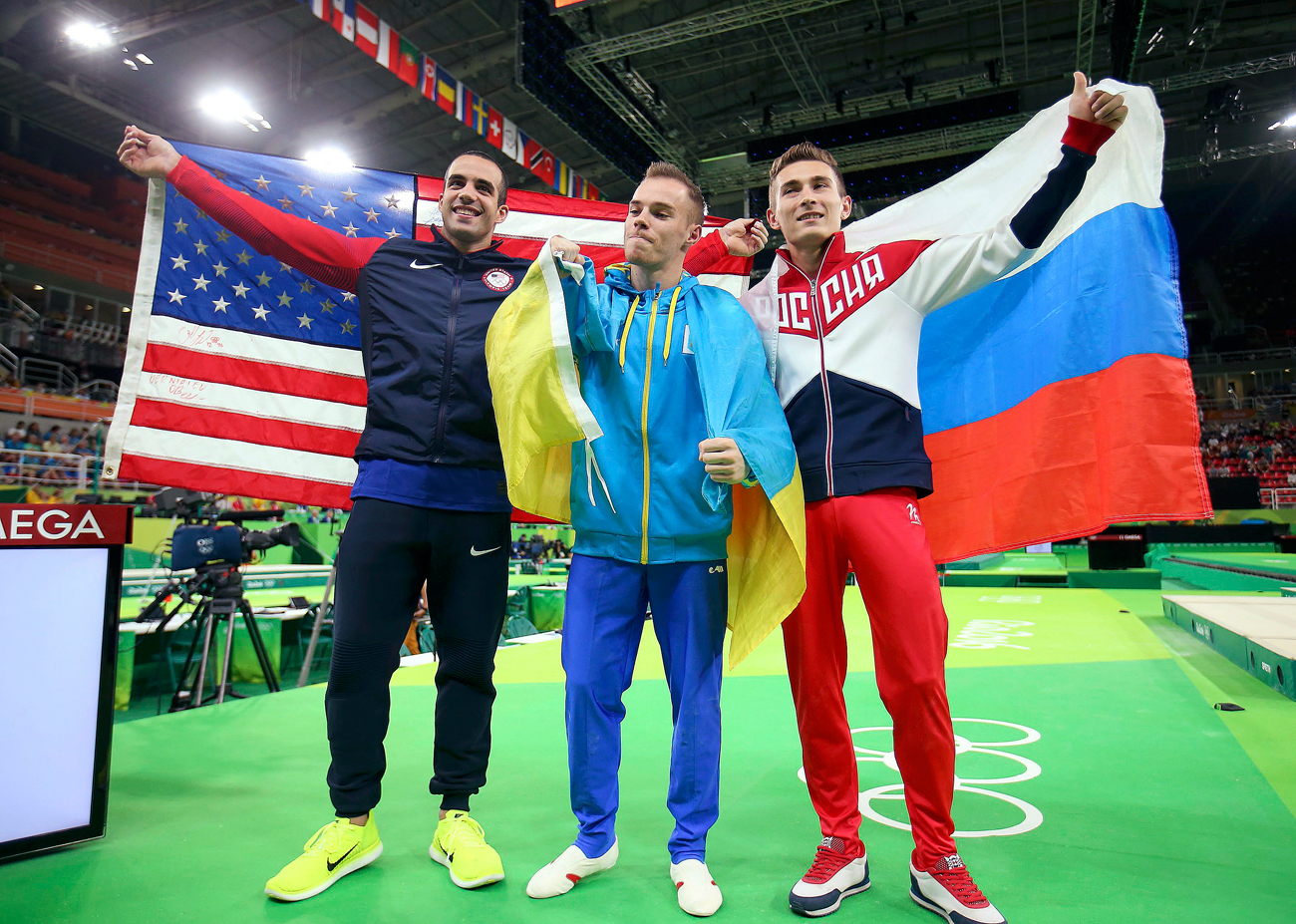 Athletes Oleg Verniaiev of Ukraine, Danell Leyva of USA, and David Belyavskiy of Russia celebrate their victory in men's parallel bars final during the Rio Olympics in Brazil.