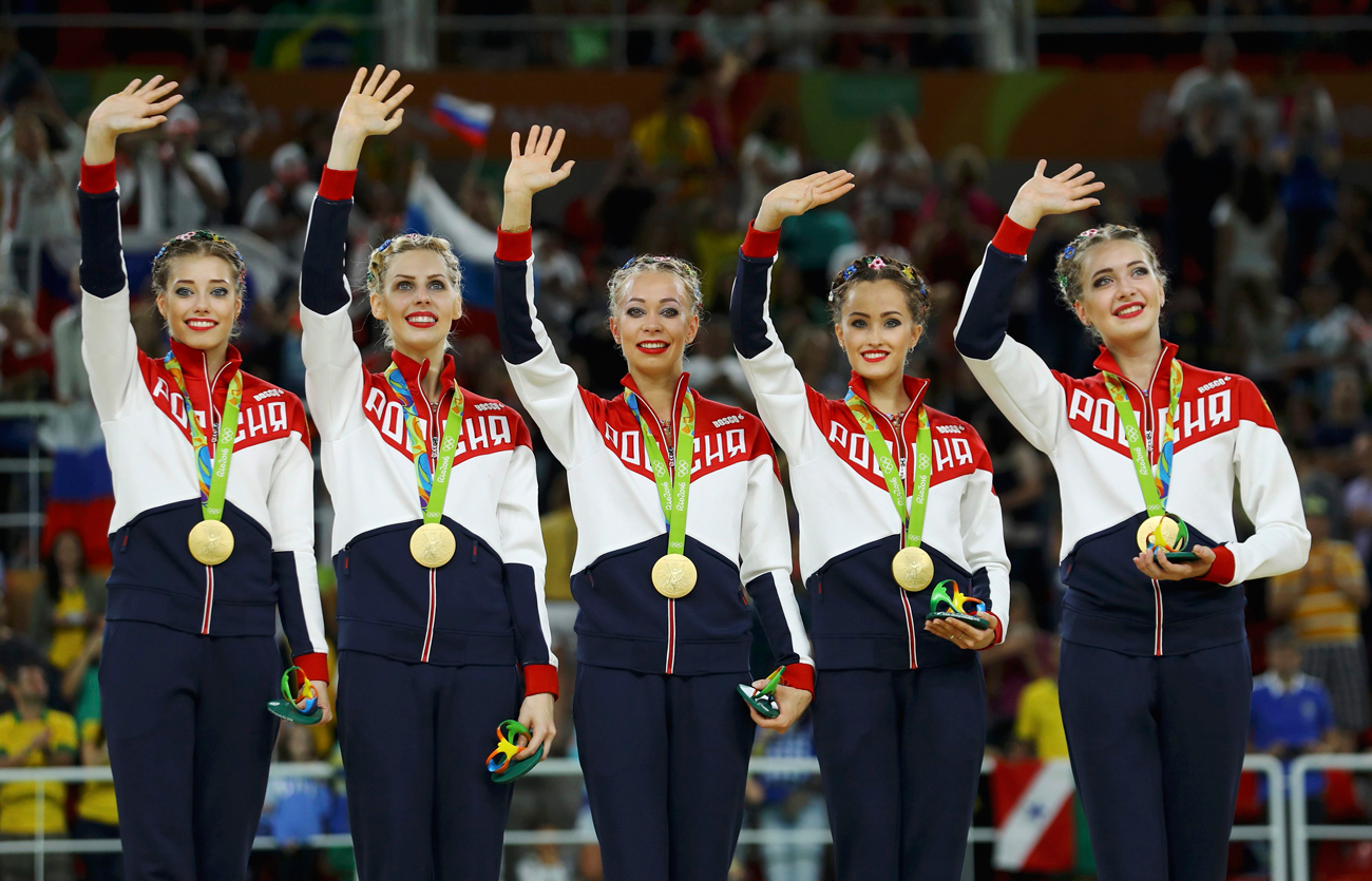 Russia's rhythmic gymnastics team pose with their gold medals on the podium, Rio Olympic Arena, Aug. 21.