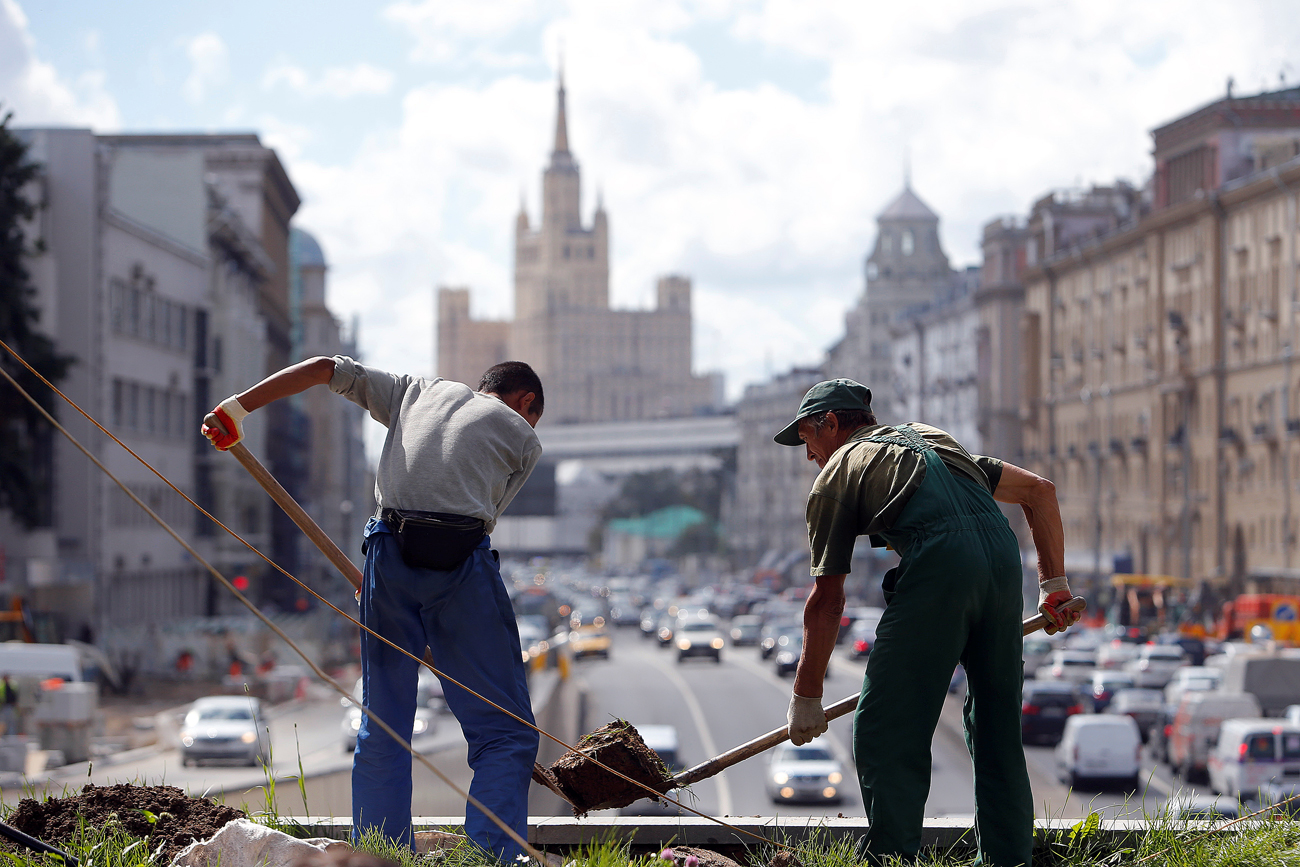 Labourers work at Triumfalnaya (Triumphal) Square as a Soviet era skyscraper is seen in the background, in central Moscow, Russia