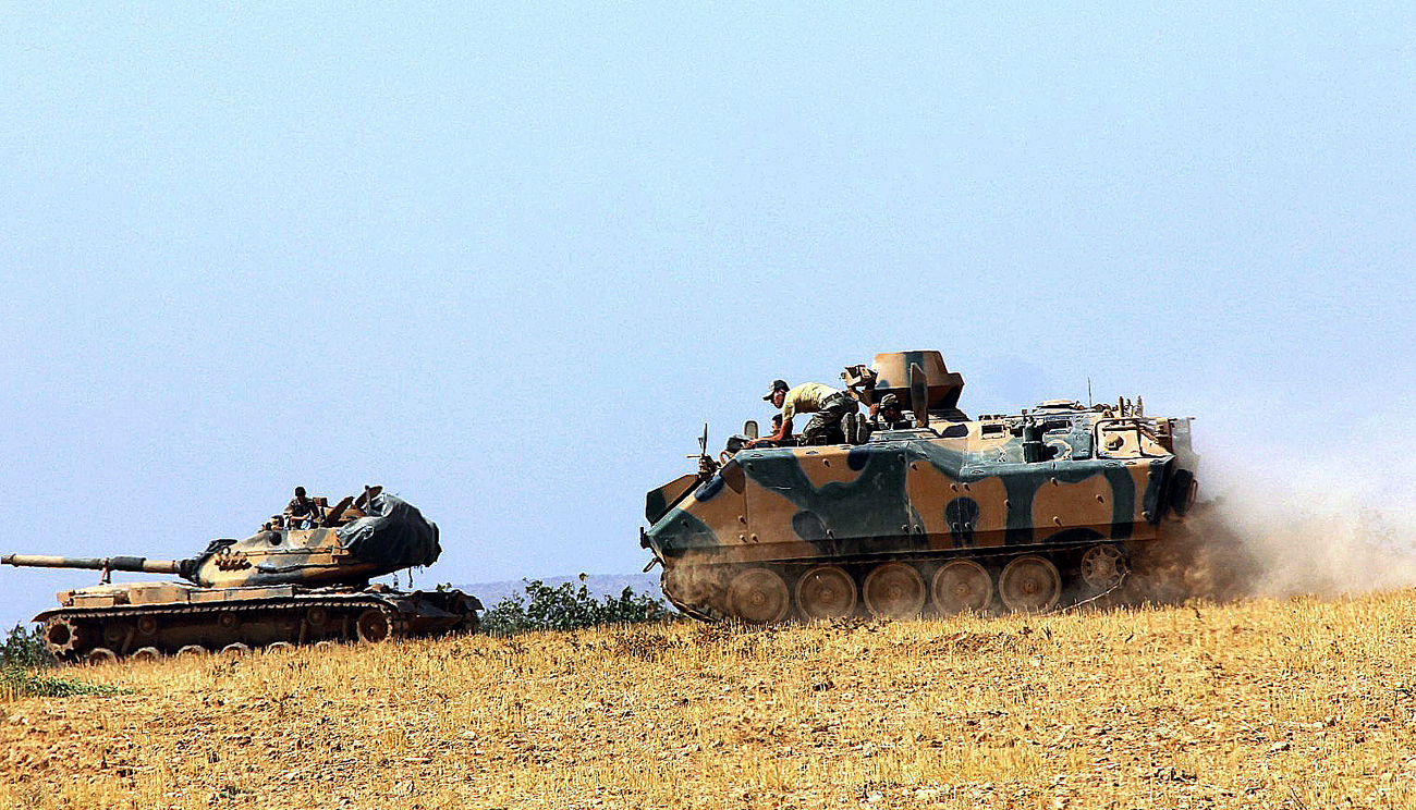 A Turkish army tank and an armored vehicle are stationed near the border with Syria, in Karkamis, Turkey.