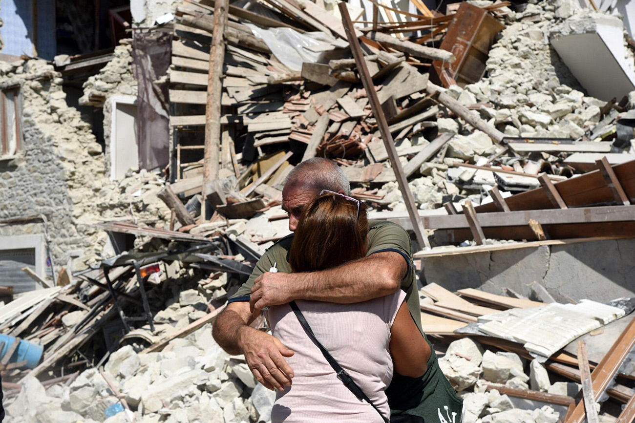 Two residents hug each other next to collapsed and damaged houses in Pescara del Tronto, central Italy, Aug. 24, 2016, following a 6.0 magnitude earthquake.