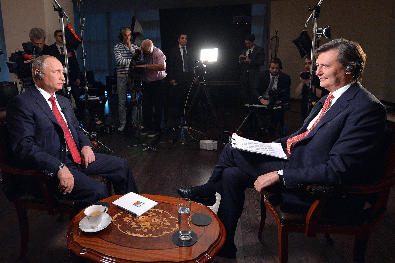 "Russian President Vladimir Putin (left) and chief editor of the Bloomberg John Mikletveyt during an interview with an international news agency ""Bloomberg"" on the island of Russian in Vladivostok, Russia."
