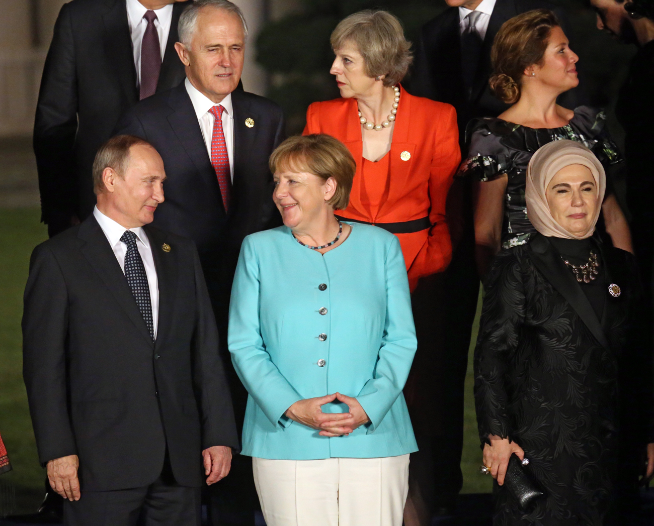 Russian President Vladimir Putin, left, speaks with German Chancellor Angela Merkel, center, while British Prime Minister Theresa May talks, center second row, during a group photo session for the G-20 Summit at Xizi Hotel in Hangzhou in eastern China's Zhejiang province / AP