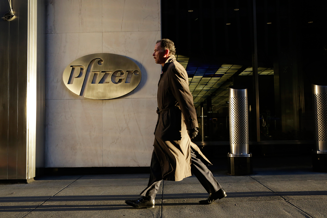 A man walks past Pfizer World Headquarters, New York.
