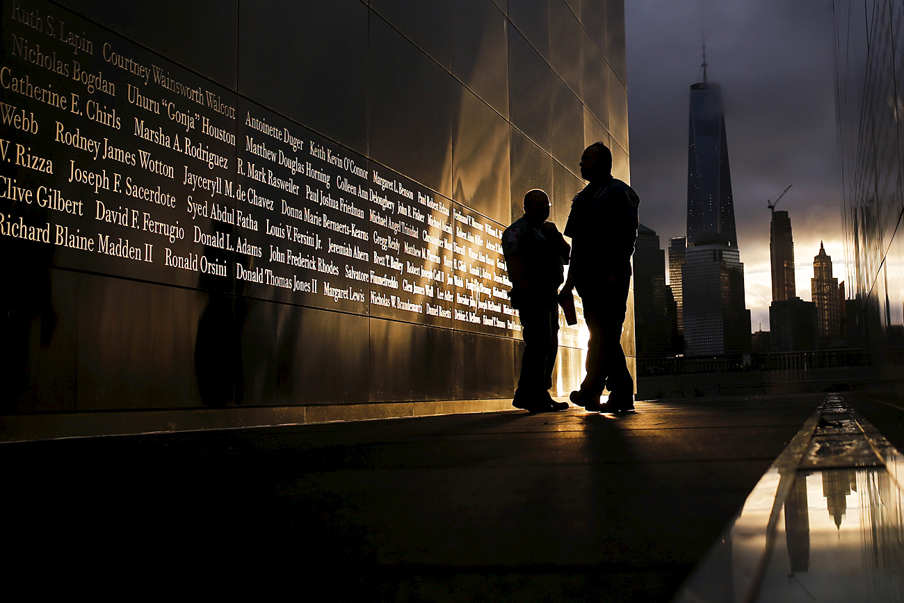People read the victims' names of the 9/11 Empty Sky memorial at sunrise across from New York's Lower Manhattan and One World Trade Center, in Liberty State Park in Jersey City, New Jersey, September 11, 2015.