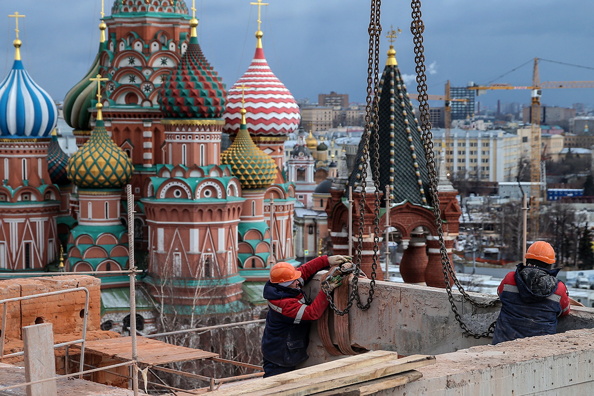 Workers seen between the Spasskaya Tower and the Senate Building of the Moscow Kremlin.