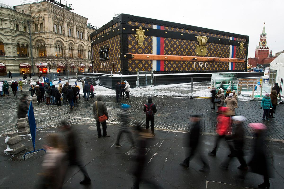 Turisti in obiskovalci hodijo mimo dvonadstropnega kovčka podjetja Louis Vuitton, ki so ga na Rdečem trgu postavili 27. novembra 2013. 9 metrov visoki in 30 metrov širok kovček so kmalu odstranili zaradi negativnih odzivov javnosti.