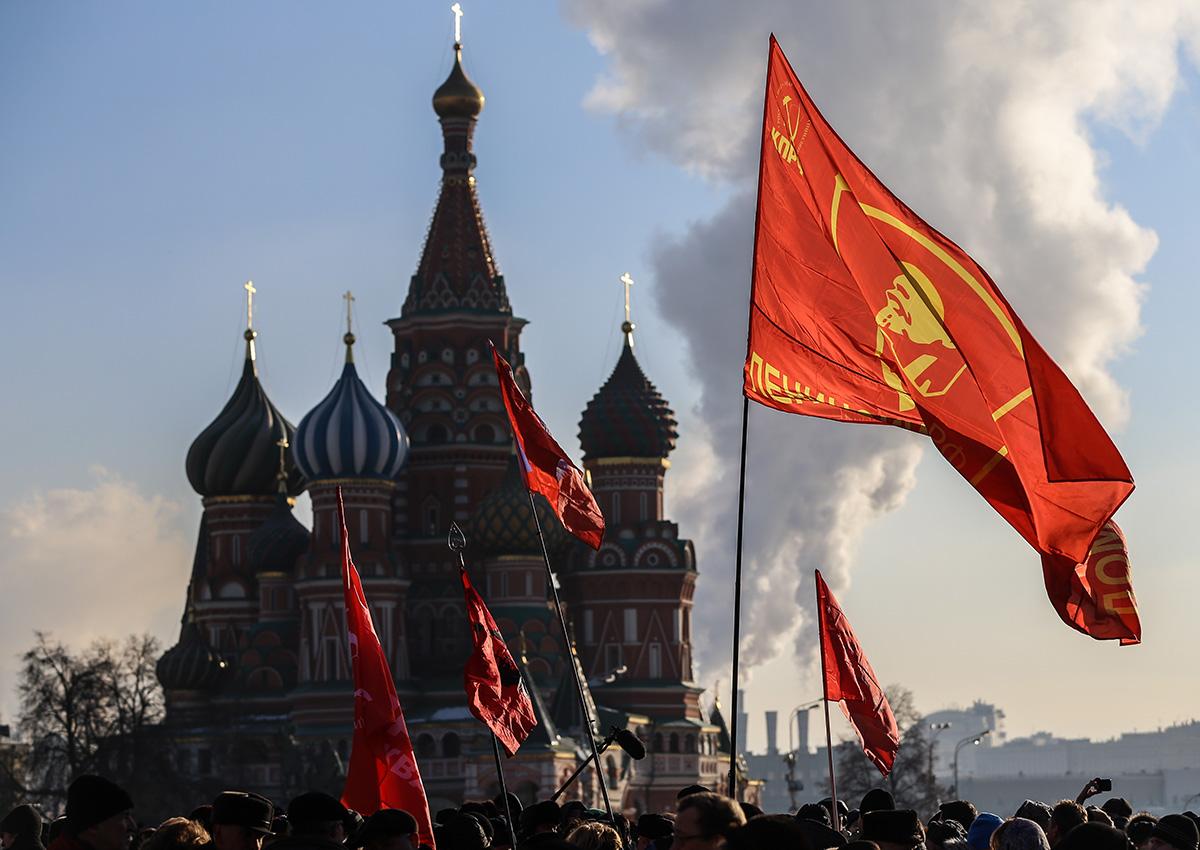 Ljudje z rdečimi komunističnimi zastavami čakajo v vrsti, da položijo rože k Leninovemu mavzoleju. Dogodek, s katerim so obeležili 91. obletnico Leninove smrti, je 21. januarja 2015 organizirala Komunistična partija Ruske federacije.