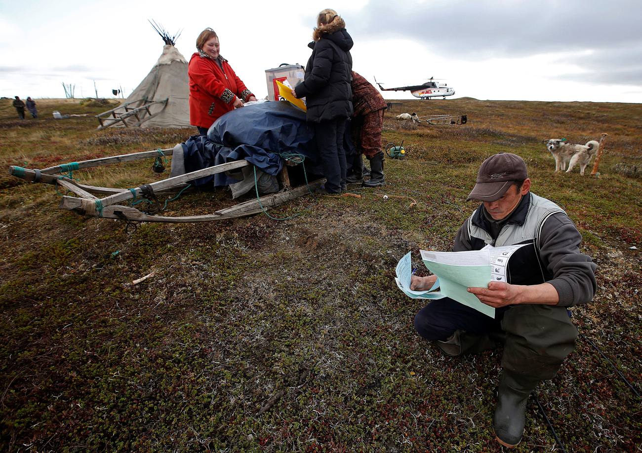 Herders fill out their ballots during early voting in the elections to the lower house of parliament in remote areas at a reindeer camping ground on the banks of the Barents Sea, north of Naryan-Mar in Nenets region, Russia