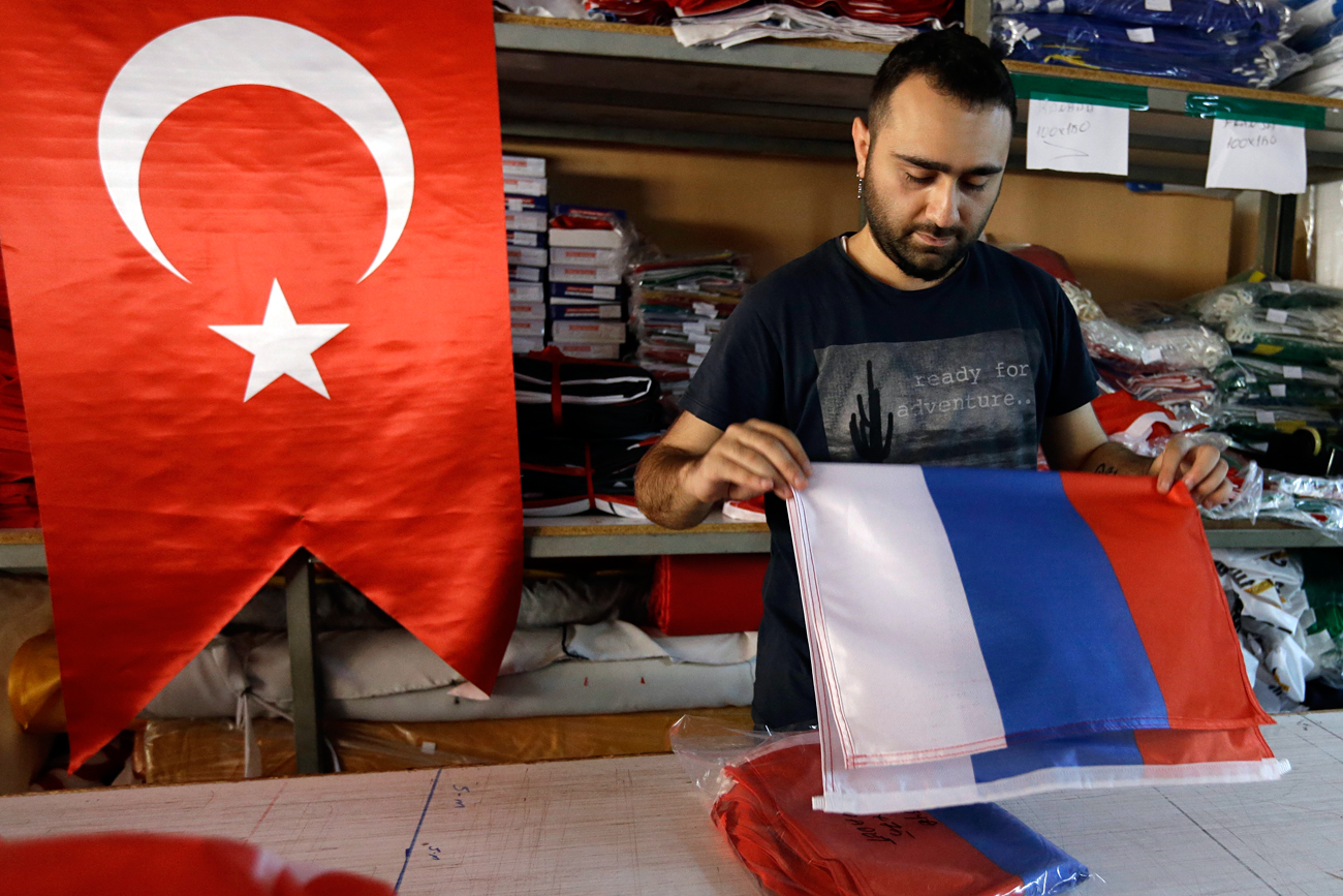 An employee of a flag-making factory folds a Russian flag as a Turkish flag adorns the display at left, in Istanbul, Tuesday, Aug. 9, 2016. The Factory production of flags has increased tenfold according to employees, as the public clamber to flay the national emblem which has become a symbol of support for the government during daily demonstrations to celebrate the suppression of a military coup. Turkey's President Recep Tayyip Erdogan arrives in Russia Tuesday for his first overseas trip since the coup attempt