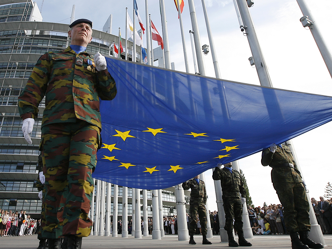Soldiers of the Eurocorps carry the European flag in front the European Parliament during a ceremony to mark the 25th anniversary of the adoption of the European flag in Strasbourg, May 9, 2011.