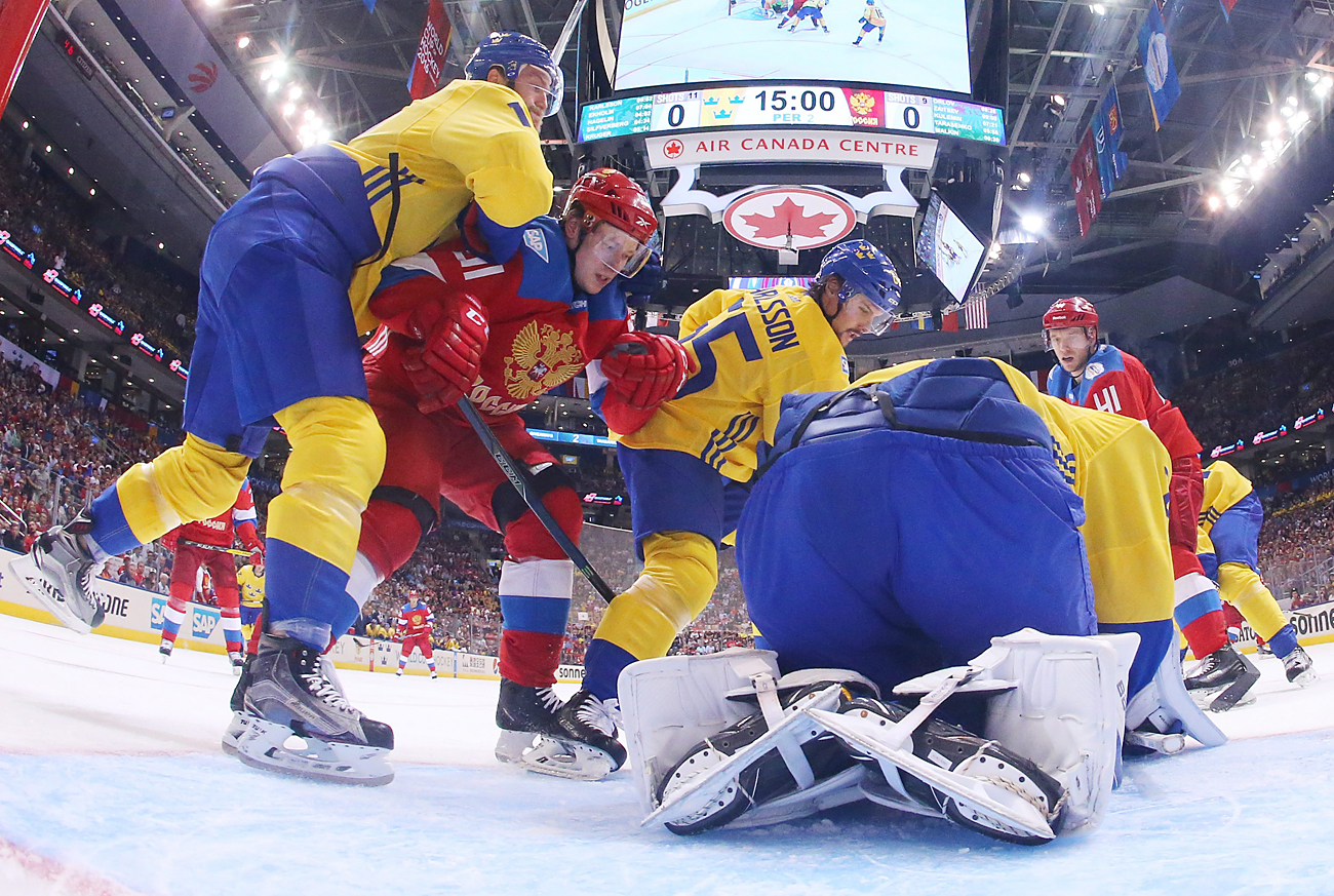 Sweden's Mattias Ekholm, left, Erik Karlsson, center, and goalie Jacob Markstrom, right, battle with Russia's Vladimir Tarasenko, second from right, during second period World Cup of Hockey action in Toronto, Sept. 18, 2016.