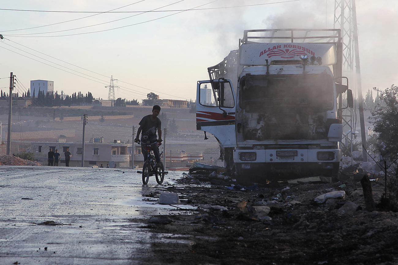 A boy rides a bicycle near a damaged aid truck after an airstrike on the rebel held Urm al-Kubra town, western Aleppo city, Syria, on Sept. 20, 2016.