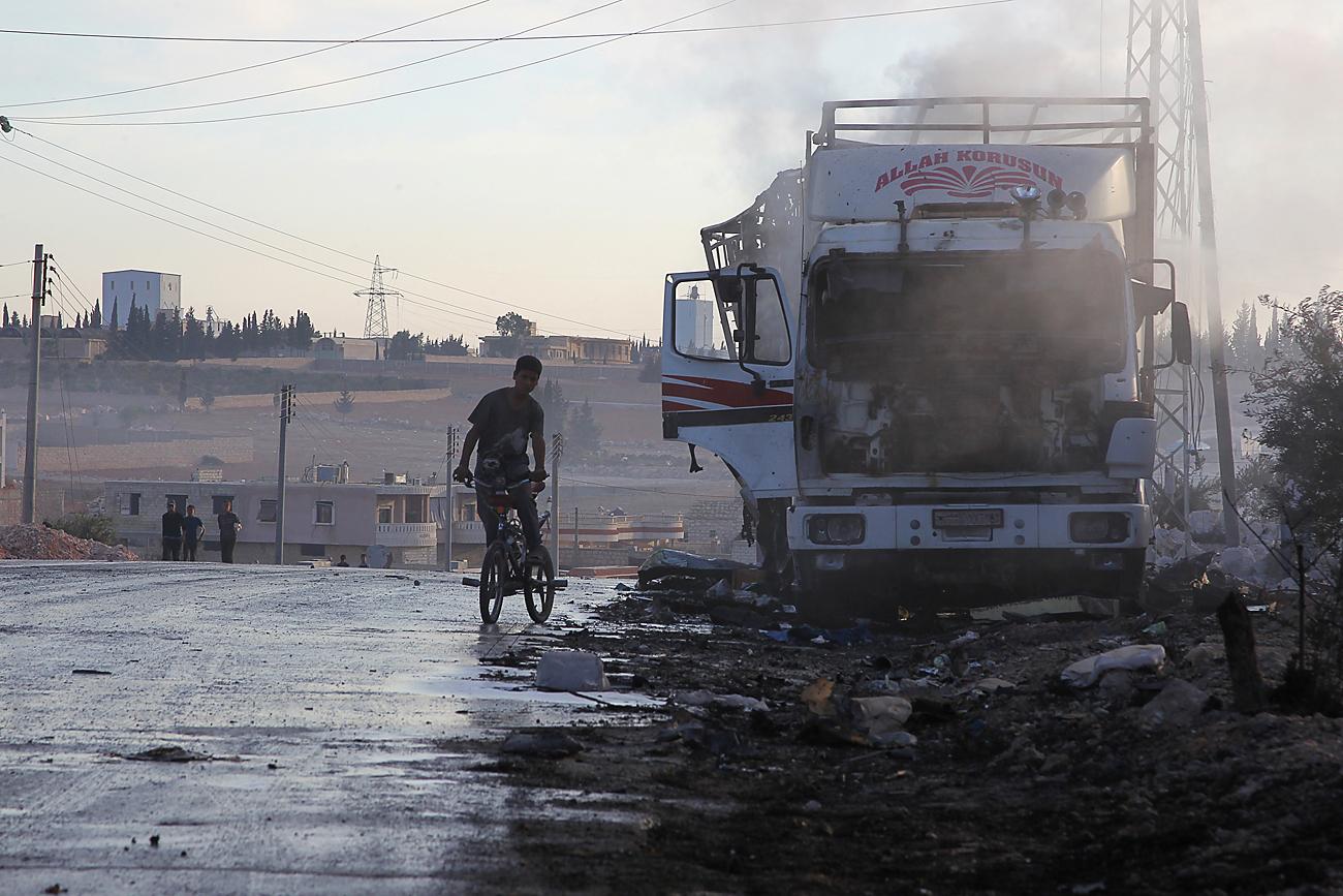 Ragazzo in sella a una bicicletta osserva un camion distrutto nella città di Urm al-Kubra, a ovest di Aleppo, in Siria.