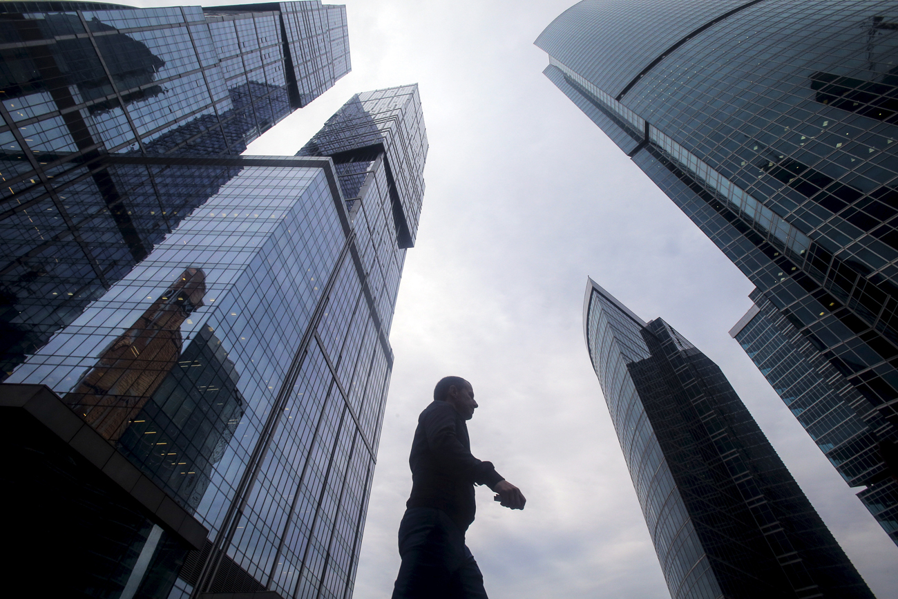 "A man walks in front of the skyscrapers of the International Business Center also known as ""Moskva-City"" in Moscow."