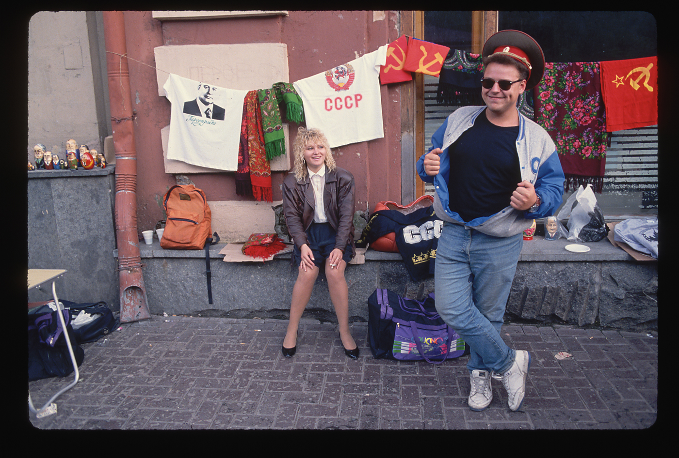 A woman and man in western style clothing near a collection of Soviet and Russian souvenirs on Arbat street, Moscow in 1991. Souvenir items include t-shirts displaying CCCP and photo of Mikhail Gorbachev.