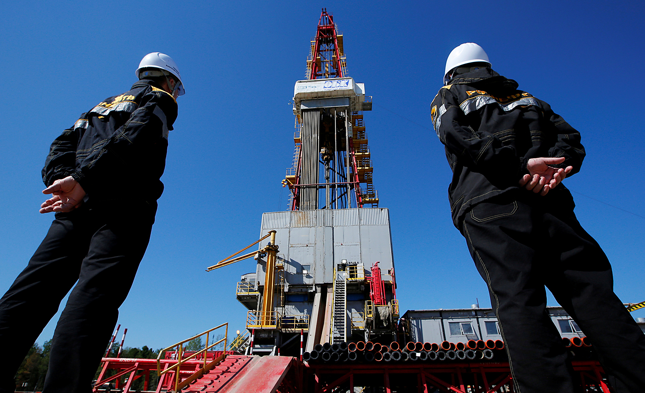 Workers look at a drilling rig at a well pad of the Rosneft-owned Prirazlomnoye oil field outside the West Siberian city of Nefteyugansk, Aug. 4, 2016.