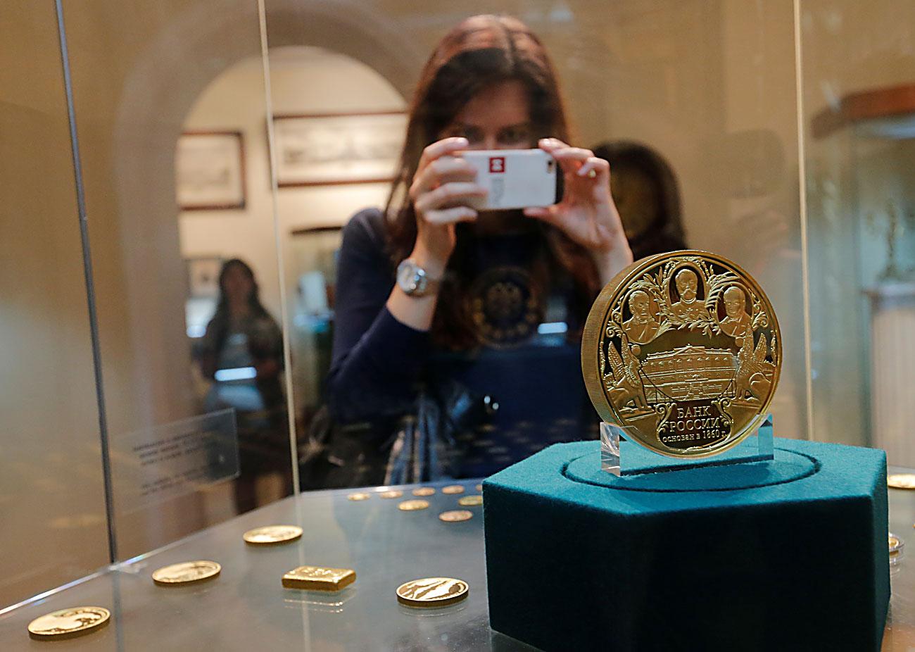 Посетител ја фотографира комеморативната монета на руска рубља од колекцијата на музејскиот и изложбен фонд во седиштетото на Централната банка во Москва, Русија.