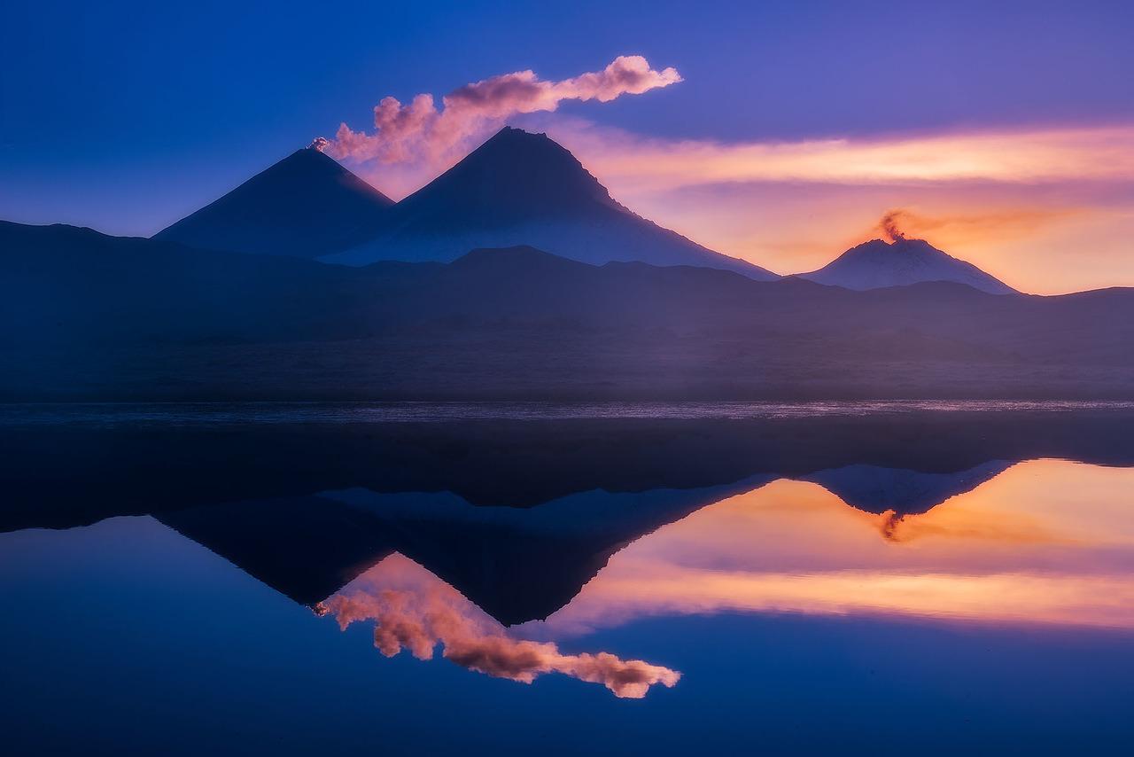 プロスキー・トルバチク火山(なだらかなトルバチク火山)とオストルイ・トルバチク火山(急なトルバチク火山)の夜明け。オストルイ・トルバチク火山は美しいが、死火山である。北斜面から見ると、プロスキー・トルバチク火山はオストルイ・トルバチク火山の肩のように見える。だがプロスキー・トルバチク火山は独立していて、活火山である。