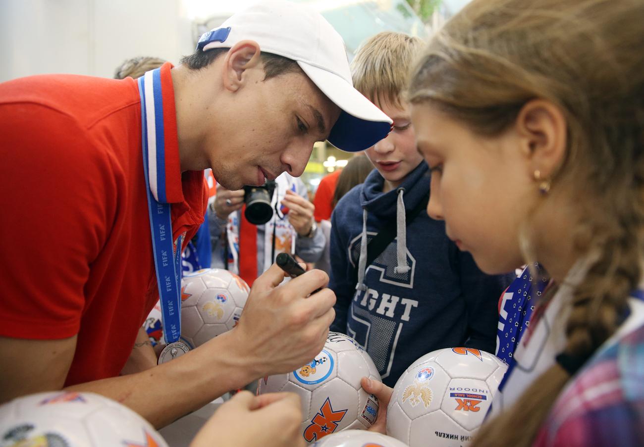 O meia Romulo distribui autógrafos durante cerimônia de boas-vindas em aeroporto russo após a prata. Foto: Mikhail Pochuyev / TASS