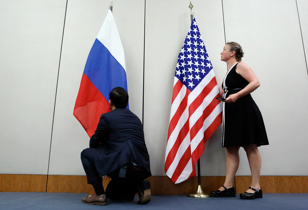 Seorang staf memasang bendera Rusia di samping bendera AS sebelum konferensi pers setelah pertemuan antara Menteri Luar Negeri AS John Kerry dan Menteri Luar Negeri Rusia Sergey Lavrov di Jenewa, Swiss, 26 Agustus 2016.