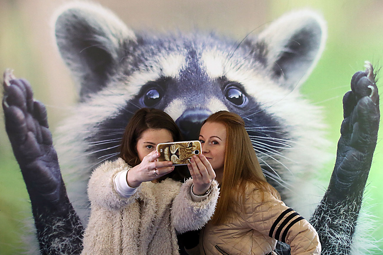 Two girls take a selfie photograph as they attend a raccoon festival at the Loft Project ETAGI cultural center and exhibition space.