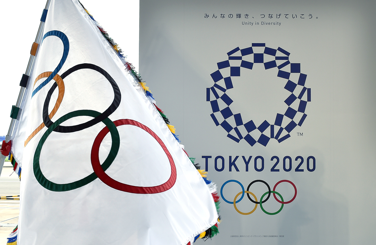 The Olympic flag (L) and the logo of the Tokyo 2020 are displayed during the official flag arrival ceremony at the Tokyo's Haneda airport.