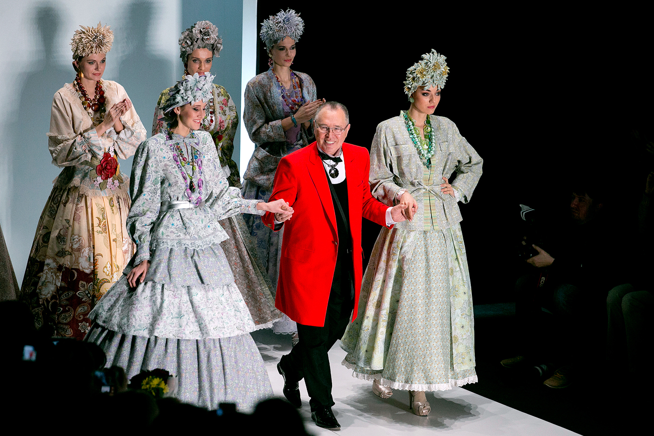 Russian designer Slava Zaitsev walks surrounded by models after a fashion show of his creations at the Russian Fashion Week in Moscow.