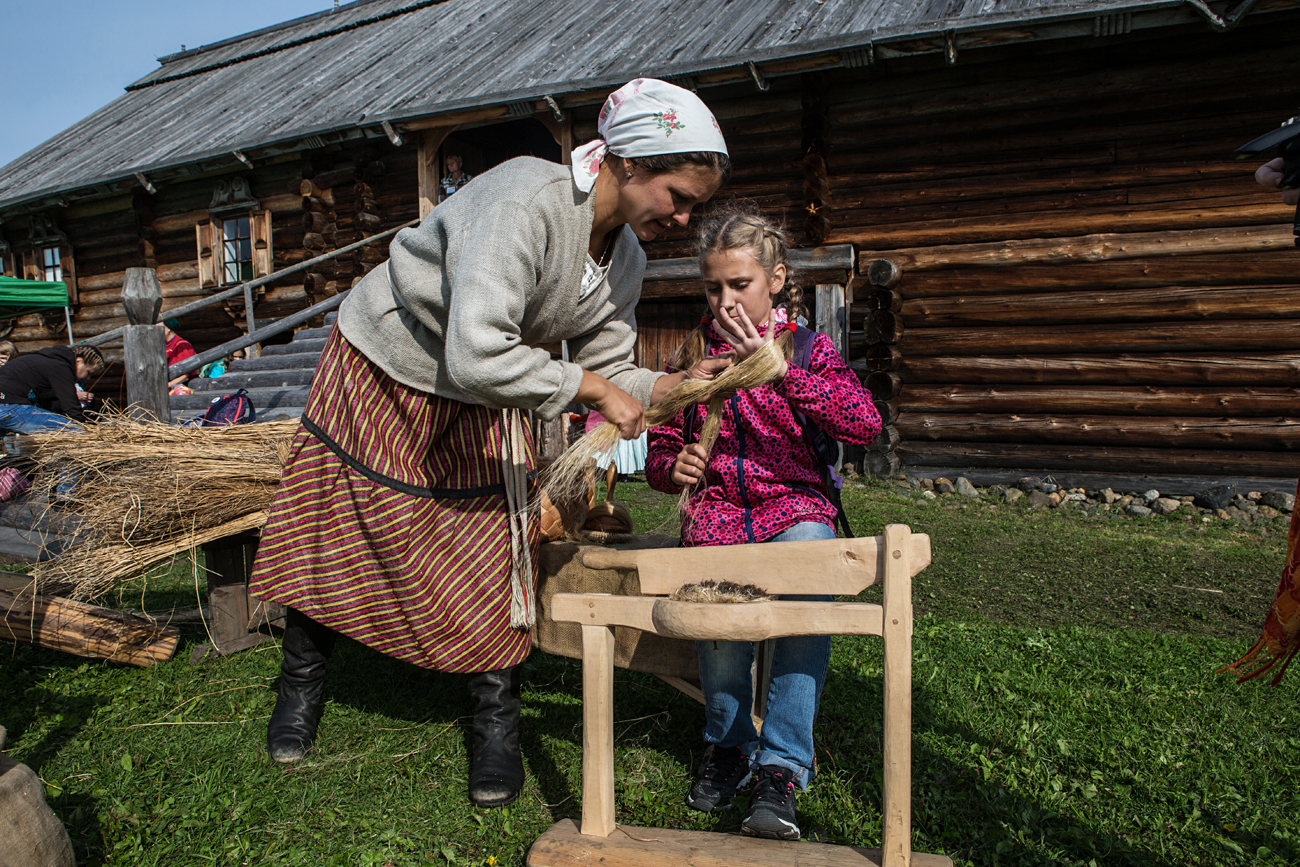 The new generation of Karelians is looking to traditional culture for ways to make identifying as Karelian trendy. Photo: Avisitors to the Kizhi museum-reserve attends a lesson on flax processing as part of the Knowledge Day celebrations.