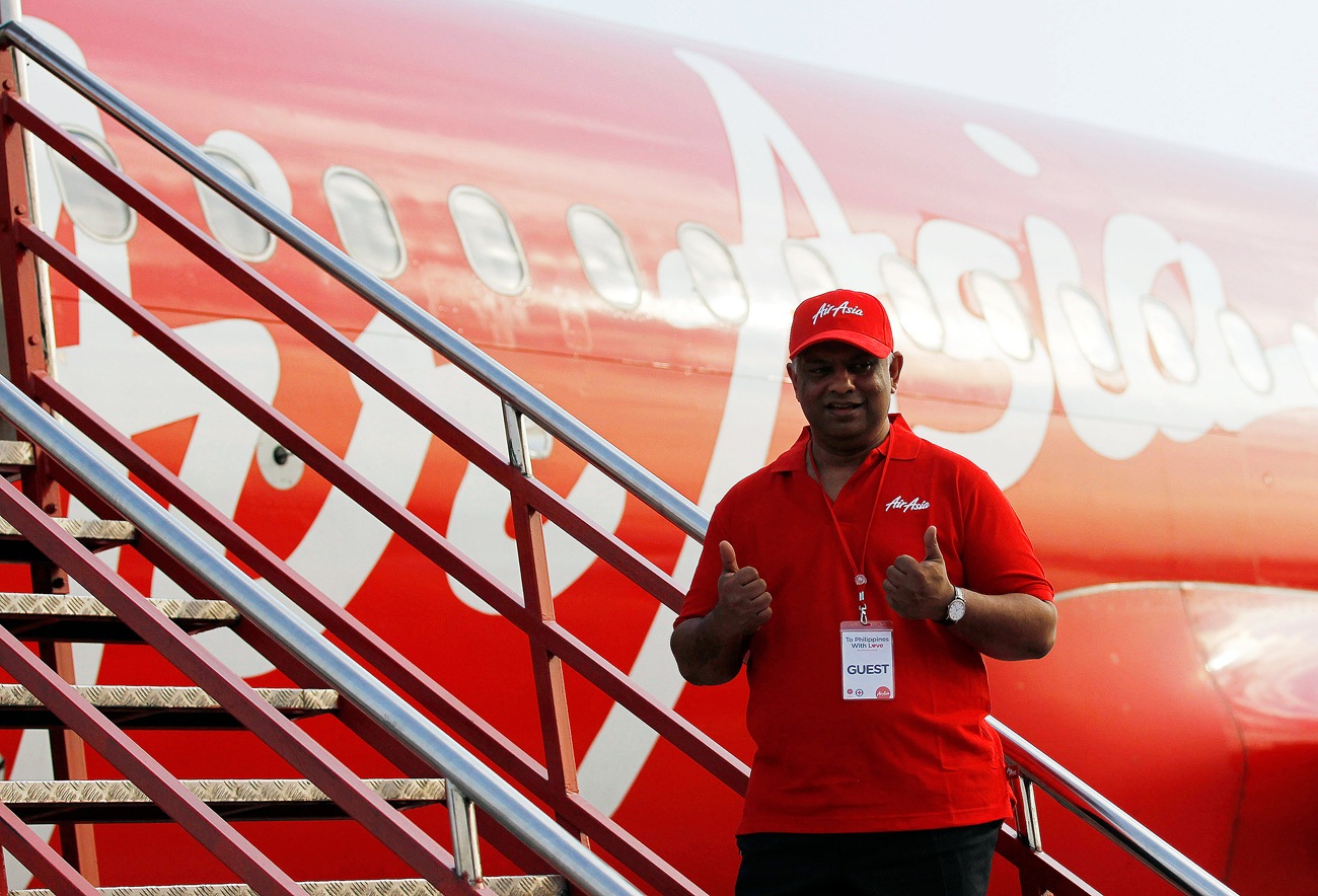 Tony Fernandes, CEO of AirAsia, gestures before boarding a AirAsia Airbus A320 plane at the domestic airport in Manila.