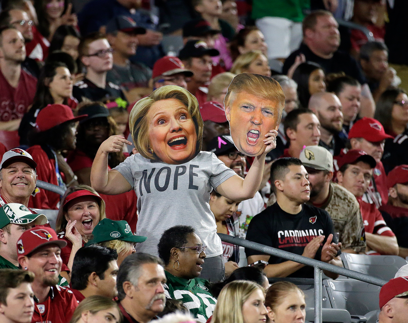 A fan wears a Hillary Clinton and holds a Donald Trump masks during the first half of an NFL football game between the New York Jets and the Arizona Cardinals.