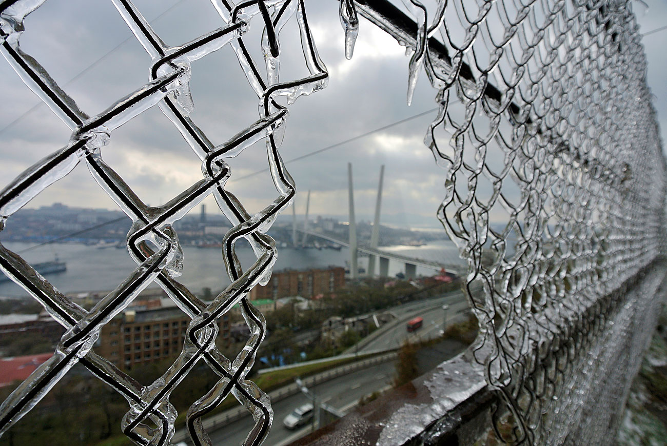 A bridge linking Russky Island with the mainland is seen through a fence covered with ice after freezing rain in the far eastern city of Vladivostok, Russia, October 22, 2016