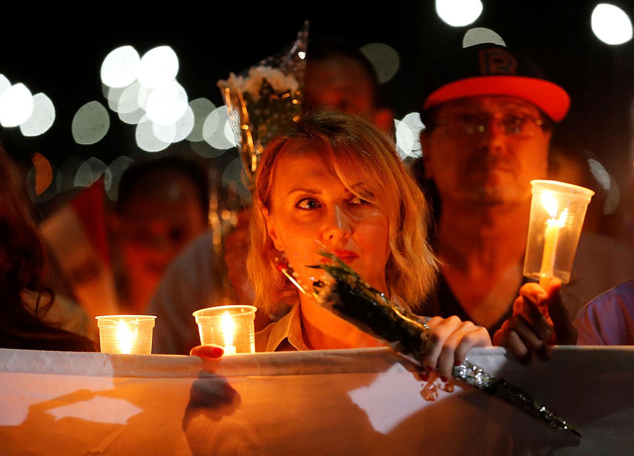 """Луѓе со свеќи и знамето на РФ на """"Плоштадот на мирот"""" во текот на церемонијата на одбележување на првата годишнина од падот на рускиот авион А321 во одморалиштето Шарм ел Шеик на Црвеното море, Египет. 30 октомври 2016."""