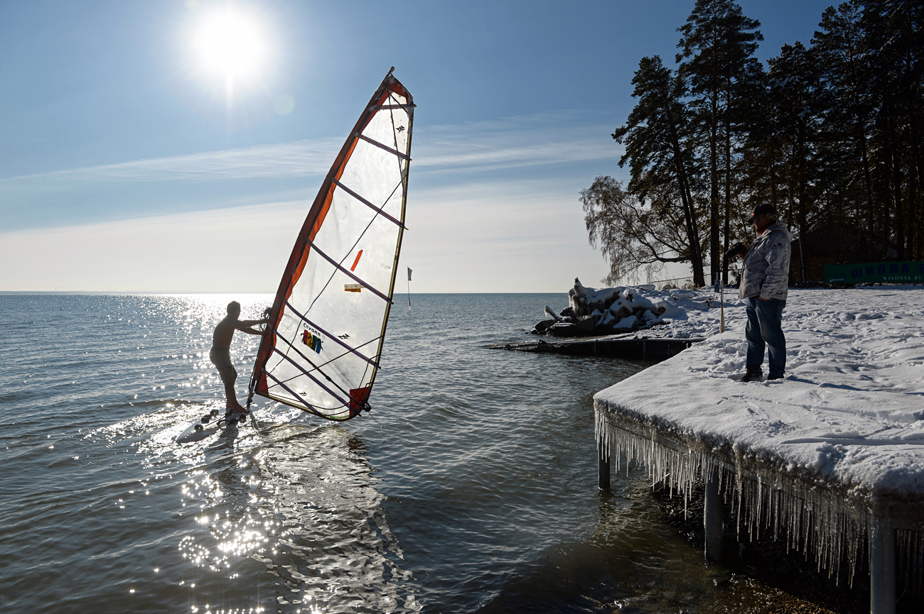 "The athlete Alexander Orlov (left) practicing windsurfing under the temperature of minus 5 Centigrade at the Novosibirsk Hydro reservoir close to the surf station ""Boomerang""."