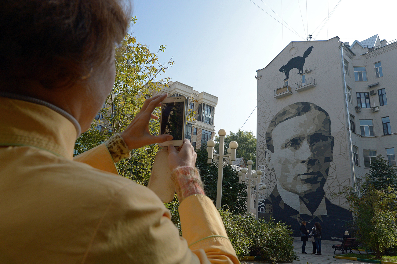A woman photographing the portrait of writer Mikhail Bulgakov on the wall of a building in Bolshoi Afanasyevsky Pereulok in Moscow.