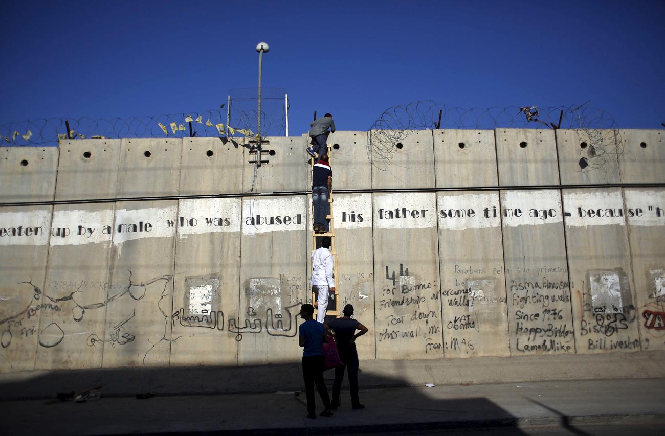 Palestinci, ki jim varnostne sile zaradi starostne omejitve ne dovolijo iz Zahodnega brega v Jeruzalem, se skušajo s pomočjo lestve prebiti čez sporni zid, da bi se v mošeji al-Aksa lahko udeležili četrte petkove molitve ob Ramadanu.