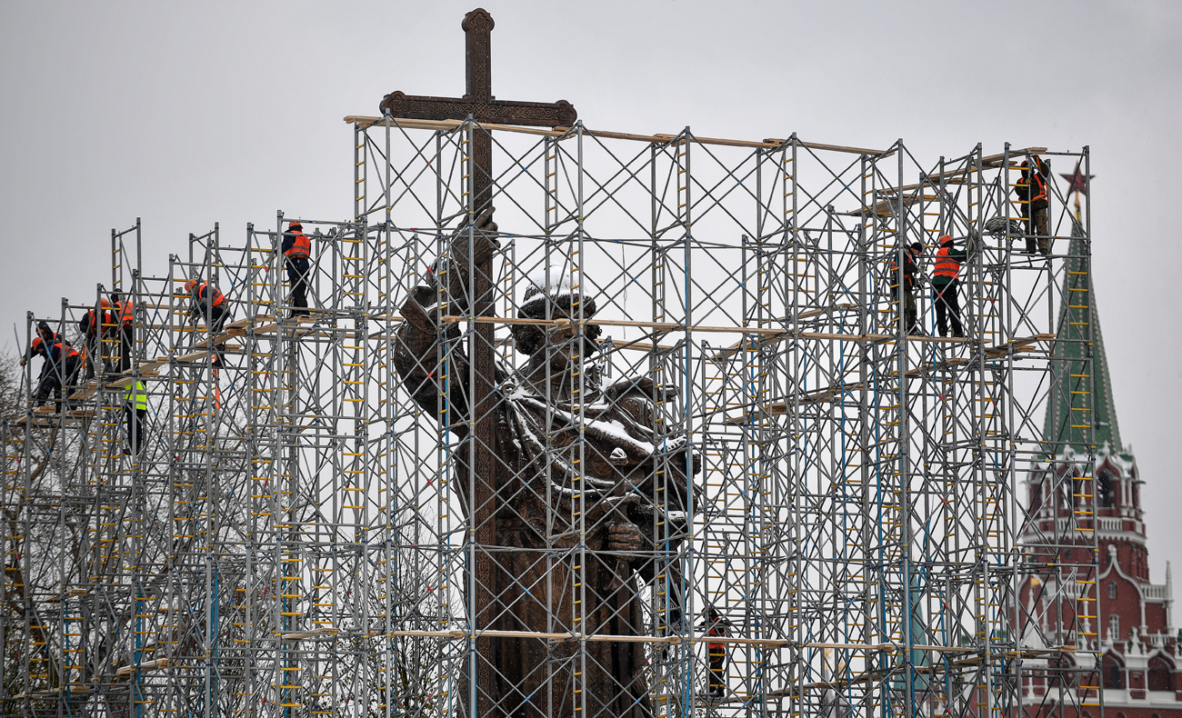 Workers seen by a monument to Prince Vladimir in Moscow.