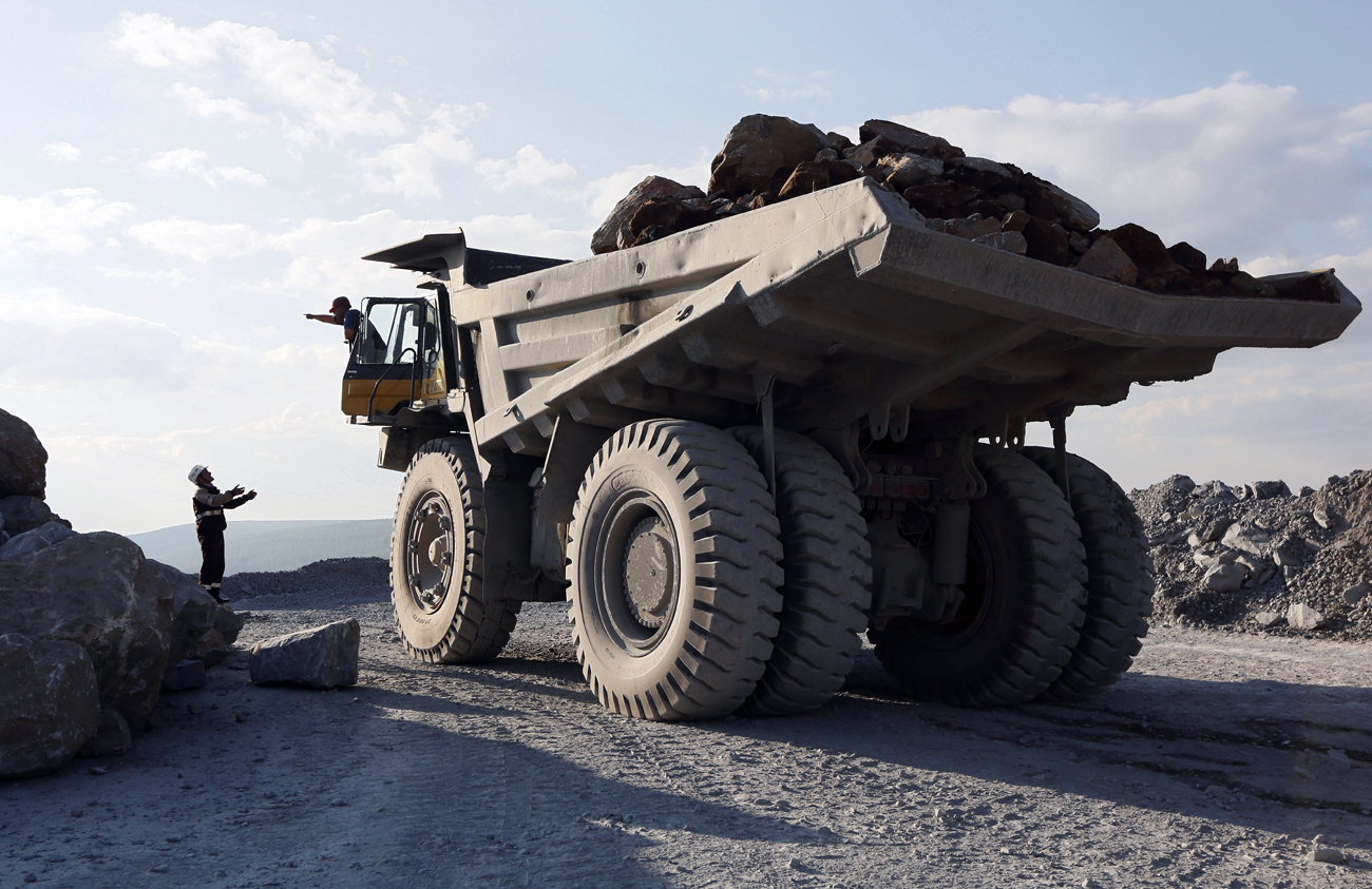 An engineer talks to a driver of a dump truck loaded with gold-bearing soil at the Vostochny opencast of the Olimpiada gold operation, owned by Polyus Gold International company, in Krasnoyarsk region.