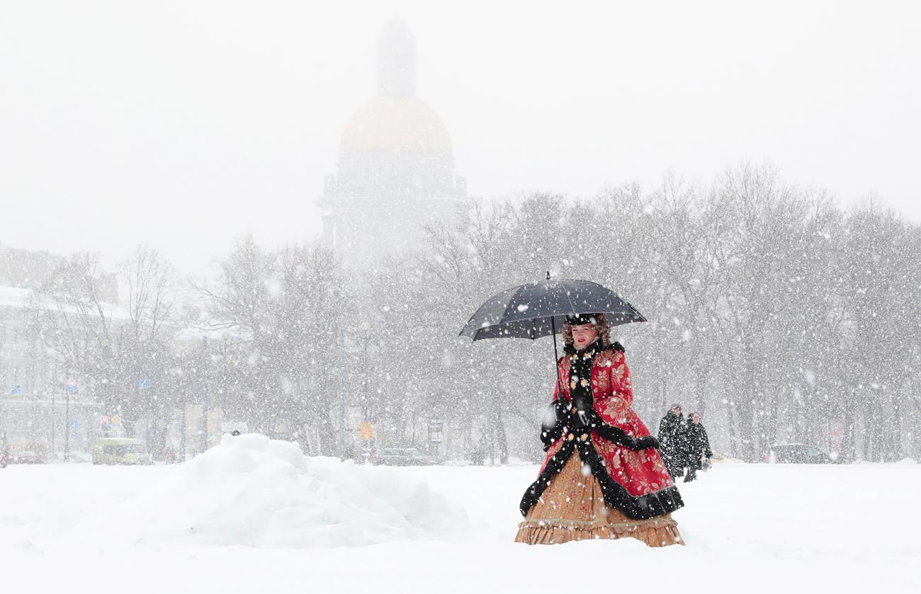 Actriz vestida con un traje de época camina por la nieve en San Petersburgo.