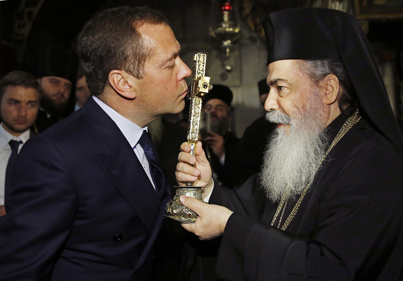 Russian Prime Minister Dmitry Medvedev, left, kisses a crucifix during a visit to the Church of the Holy Sepulchre in Jerusalem, Israel on Thursday, Nov. 10. 2016. Medvedev is on a high level visit to Israel to explore issues of mutual interest.