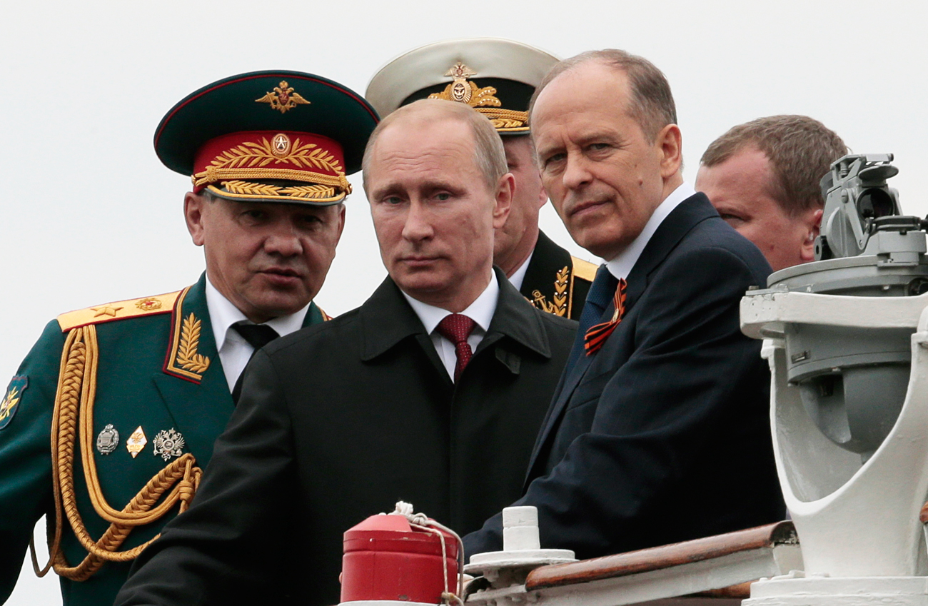 Russian President Vladimir Putin flanked by Defense Minister Sergei Shoigu, left, and Federal Security Service Chief Alexander Bortnikov on May 9, 2014.