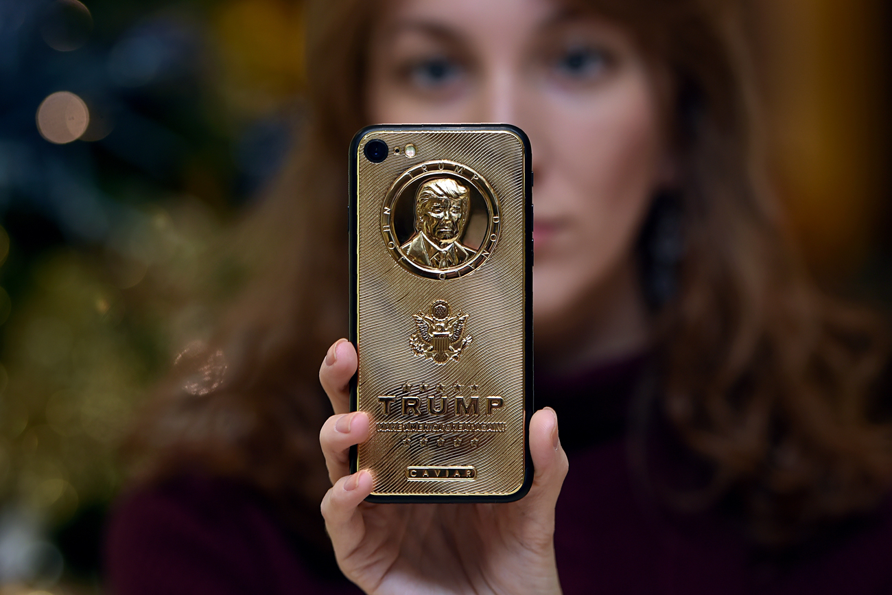 An employee of Caviar Phones, a Russian-Italian company specializing in smartphone customization, displays a special gold-plated iPhone 7 smartphone bearing the likeness of US President-elect Donald Trump - at a minimum price of 197,000 rubles (2,755 euros or 2,971 dollars) - in the company's boutique outside Moscow.