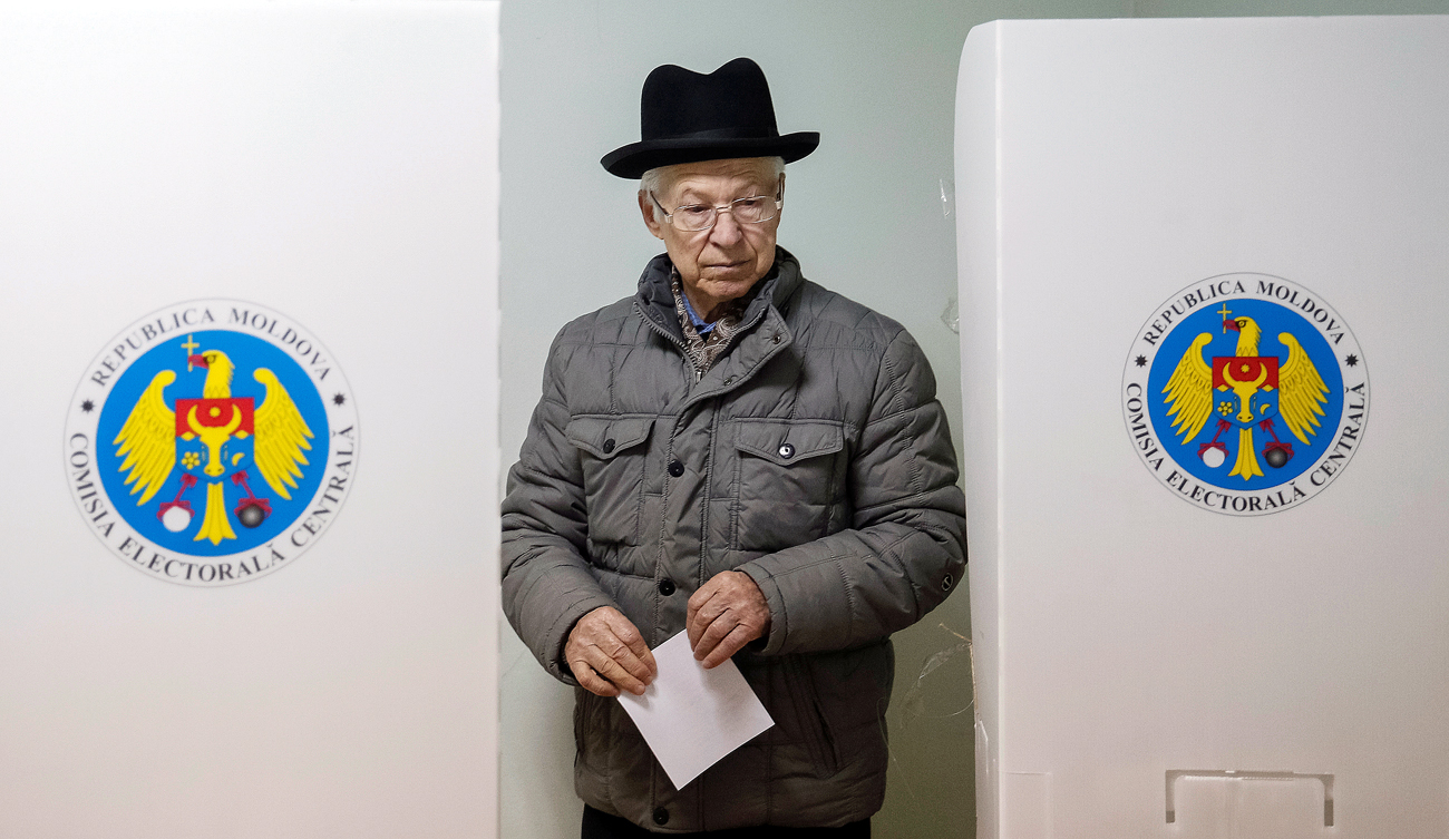 A man leaves a booth before casting his vote during a presidential election at a polling station in Chisinau, Moldova