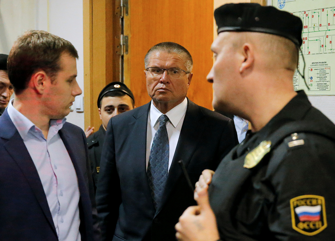 Russian Economy Minister Alexei Ulyukayev who was detained by law enforcement officials on corruption charges, is escorted upon his arrival for a hearing at the Basmanny district court in Moscow, Nov. 15, 2016.