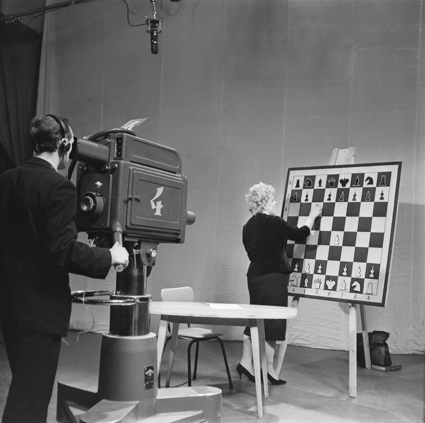 1964. A women analyzes a chess game during a TV show.