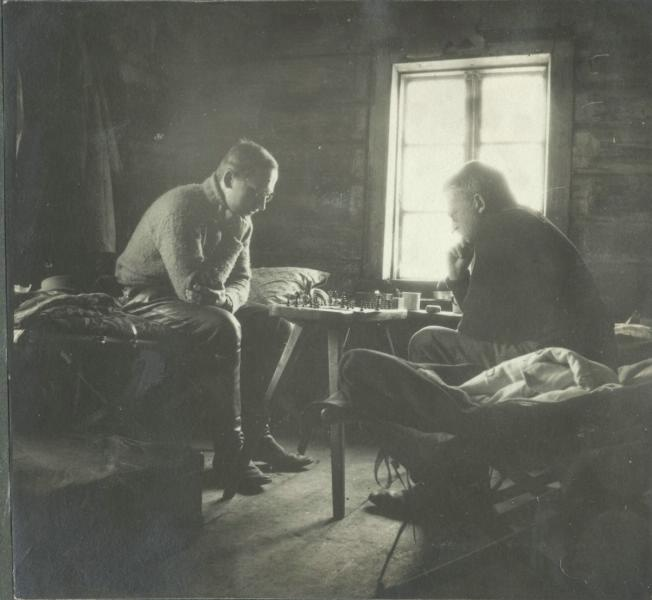 1914-1918. Two men play chess in a wooden country house.